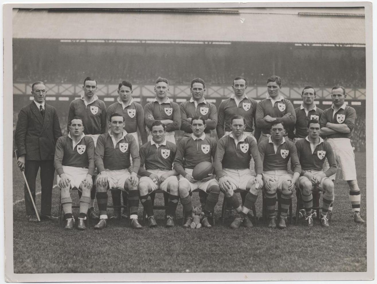 Black and white photograph of 15 players in rugby kit and 1 official in a suit and tie