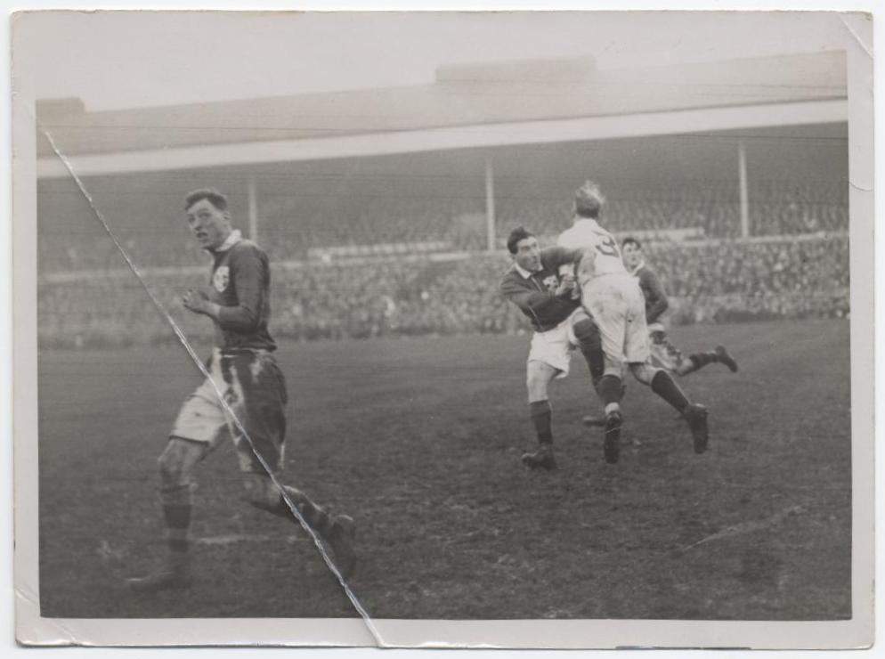 Black and white photograph of the match. 2 players collide.